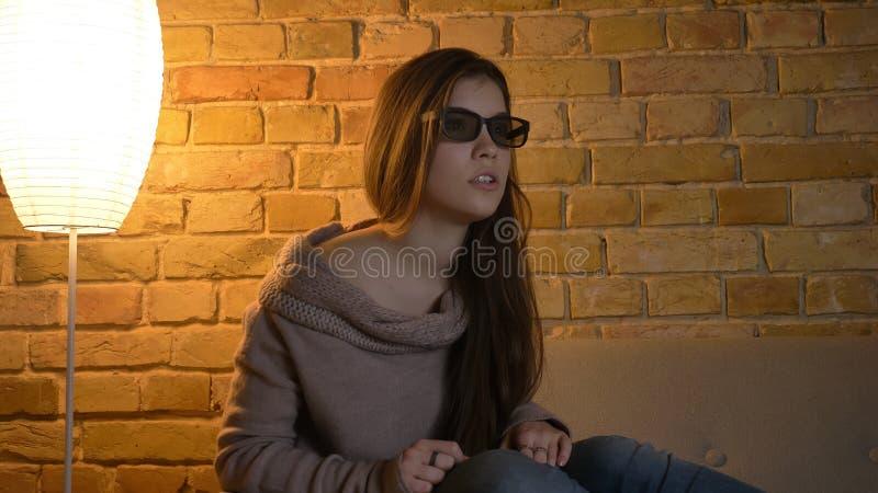 Nahaufnahmeporträt der jungen netten kaukasischen Frau, die im Fernsehen einen Film in den Gläsern 3D mit fasziniertem Gesichtsau lizenzfreies stockfoto