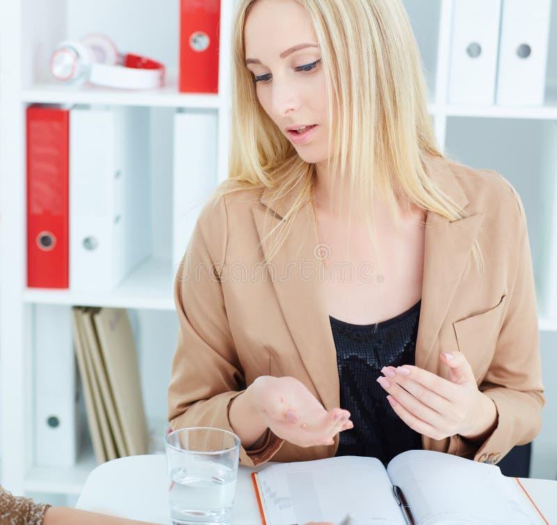 Nahaufnahmeporträt der jungen schönen ernsten Geschäftsfrau, die etwas Teilhaber erklärt stockbild
