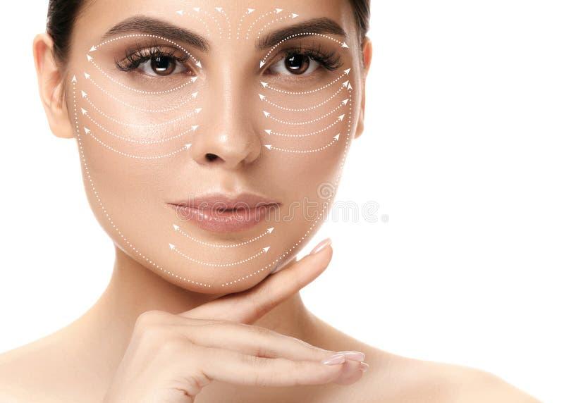 Nahaufnahmeporträt der jungen, schönen und gesunden Frau mit Pfeilen auf ihrem Gesicht stockfotos