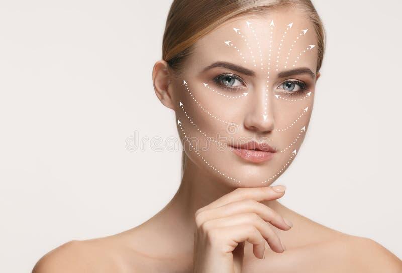 Nahaufnahmeporträt der jungen, schönen und gesunden Frau mit Pfeilen auf ihrem Gesicht lizenzfreies stockfoto