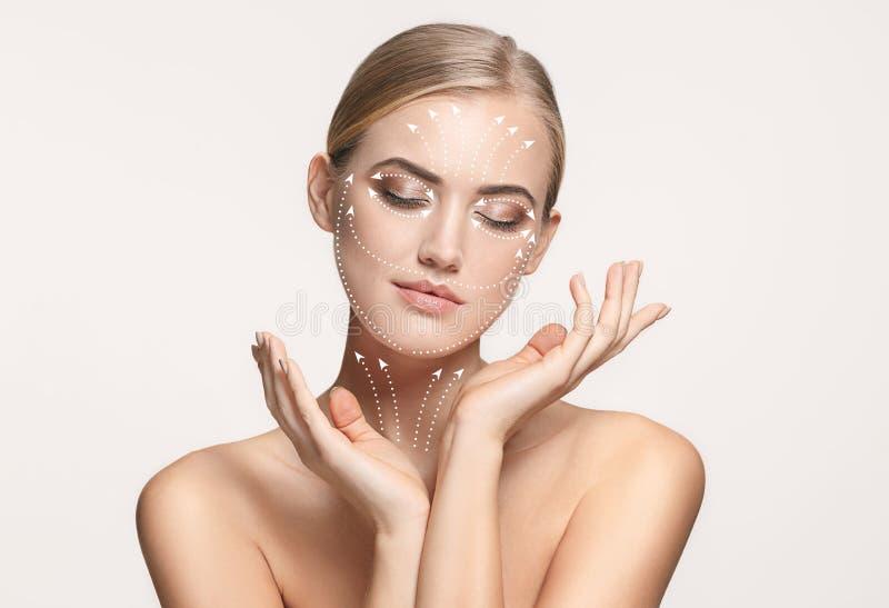 Nahaufnahmeporträt der jungen, schönen und gesunden Frau mit Pfeilen auf ihrem Gesicht lizenzfreie stockbilder