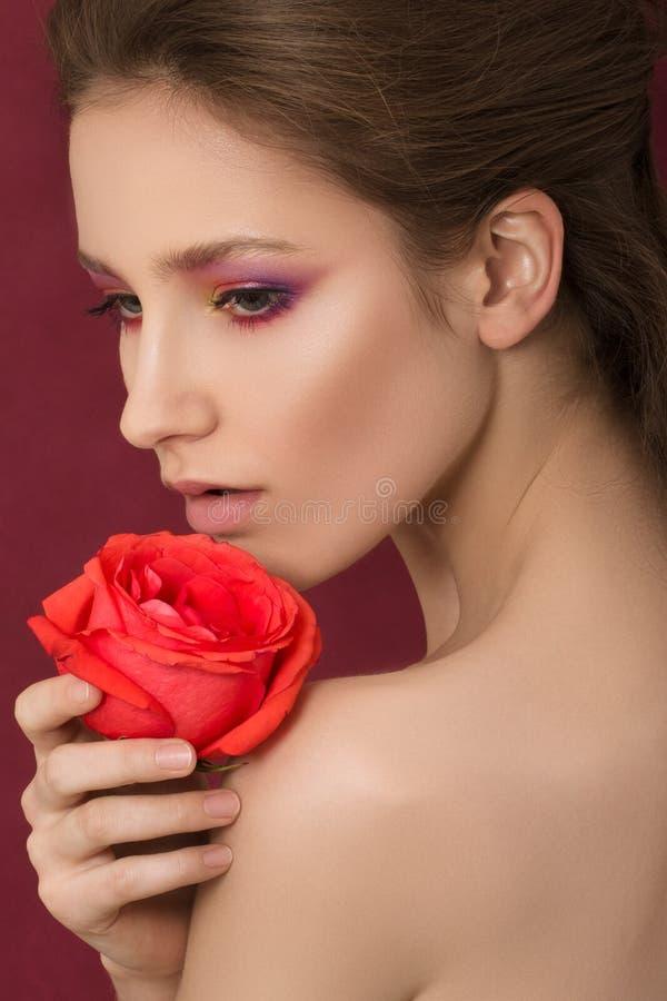 Nahaufnahmeporträt der jungen Schönheit Rotrose halten lizenzfreie stockbilder