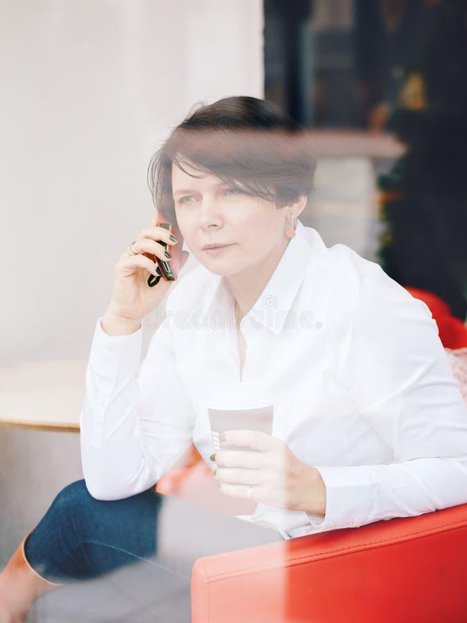 Nahaufnahmeporträt der kaukasischen weißen Geschäftsfrau des Mittelalters, die im Caférestaurant mit dem Tasse Kaffee vorbei spri stockfoto