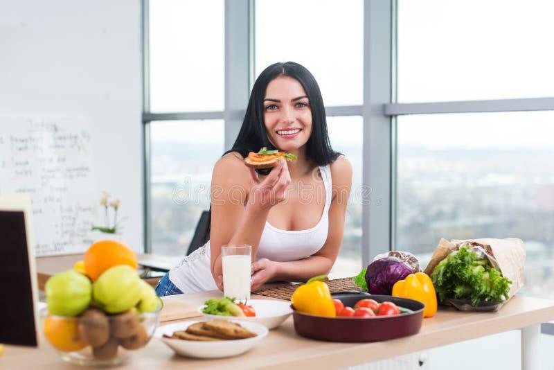 Nahaufnahmeporträt der lächelnden Frau vegetarisches Sandwich der Diät mit dem Gemüse zum Frühstück am Morgen essend, betrachtend lizenzfreie stockbilder