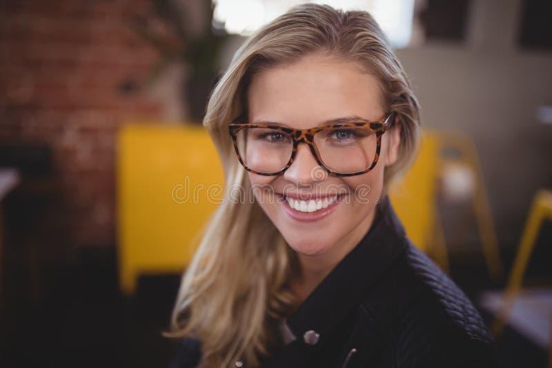 Nahaufnahmeporträt der lächelnden jungen attraktiven Frau mit Brillen lizenzfreies stockfoto