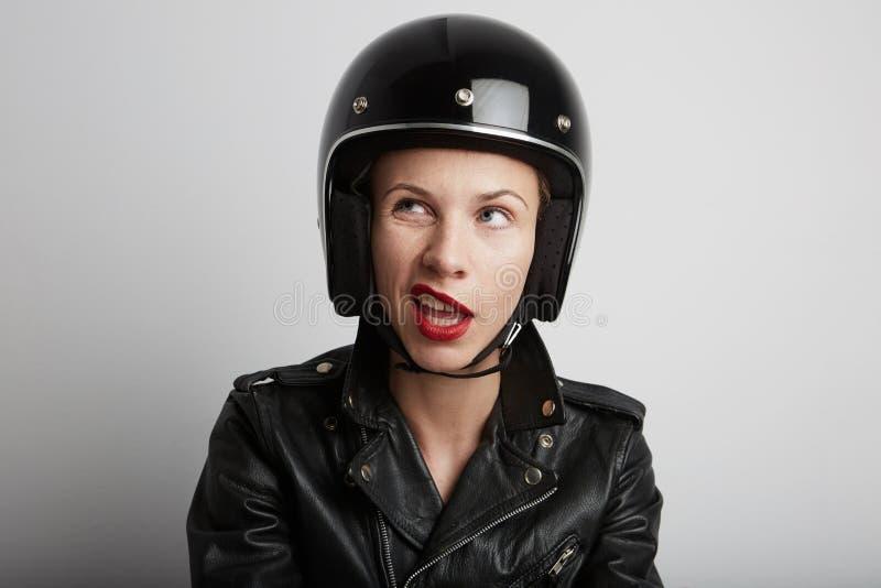 Nahaufnahmeporträt der Radfahrerfrau über weißem Hintergrund, tragendem stilvollem schwarzem sportivem Sturzhelm und Lederjacke stockfotografie