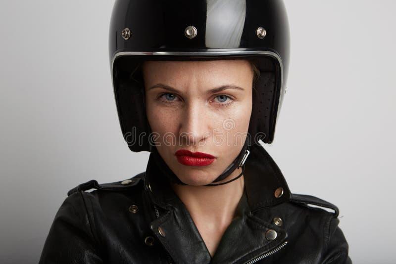 Nahaufnahmeporträt der Radfahrerfrau über weißem Hintergrund, tragendem stilvollem schwarzem sportivem Sturzhelm und Lederjacke stockfotos