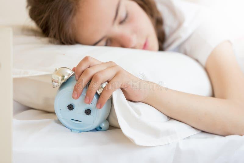 Nahaufnahmeporträt der schönen Jugendlichen schlafend und Hand auf Wecker halten lizenzfreie stockfotos