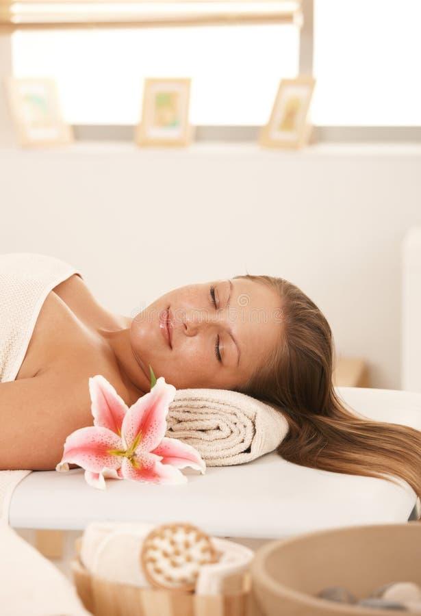 Nahaufnahme der jungen Frau stillstehend auf Massagebett stockbild