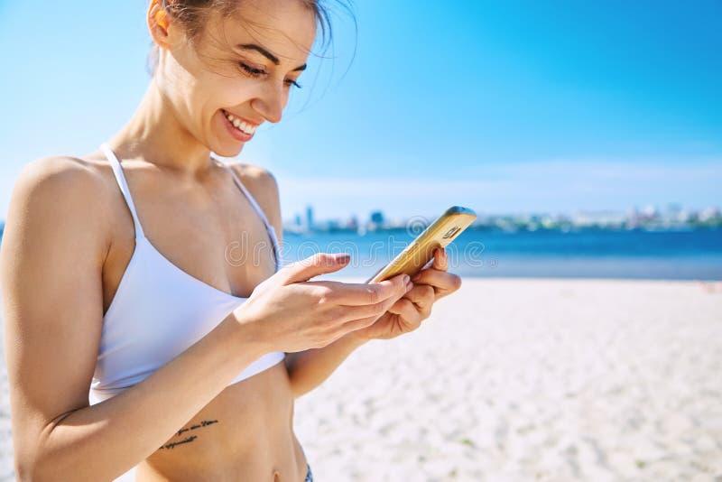 Nahaufnahmeporträt der schönen sexy glücklichen Frau auf dem Sandstadtstrand mit Seehintergrund, Telefon und das Lächeln betracht lizenzfreie stockbilder