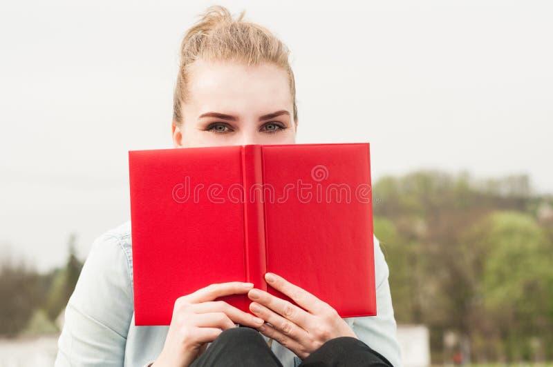 Nahaufnahmeporträt der Schönheit versteckend hinter rotem Buch stockbild