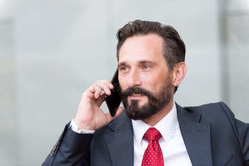 Nahaufnahmeporträt des überzeugten Geschäftsmannes kleidete in der Klage sprechend am Handy an, der draußen über grauem Hintergru lizenzfreies stockbild