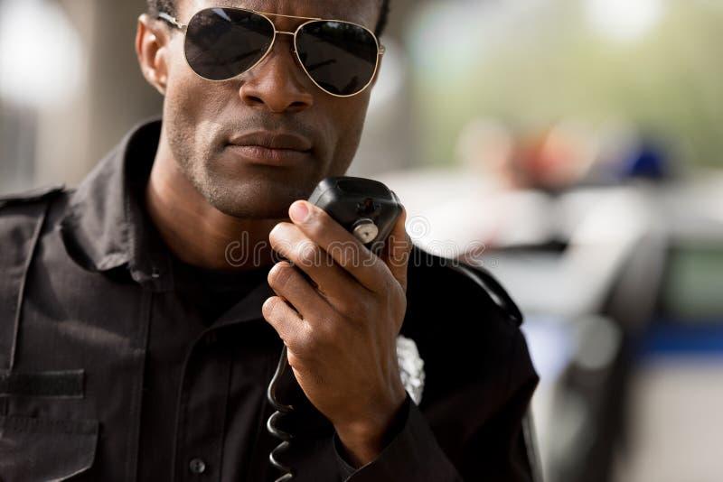 Nahaufnahmeporträt des Afroamerikanerpolizeibeamten sprechend durch Funksprechgerät lizenzfreie stockfotos