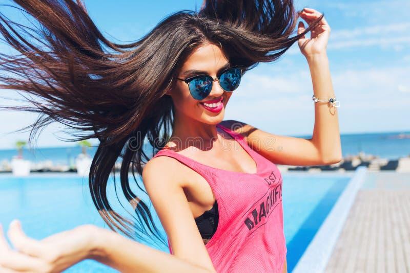 Nahaufnahmeportr?t des attraktiven brunette M?dchens mit dem langen Haar, das zur Kamera nahe Pool springt Sie tr?gt rosa T-Shirt stockbilder