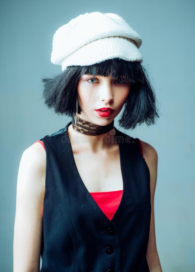 Nahaufnahmeporträt des ausgezeichneten jungen Mädchens in der dunklen Weste und in der weißen Strickmütze, schauend auf der Kamer lizenzfreies stockfoto
