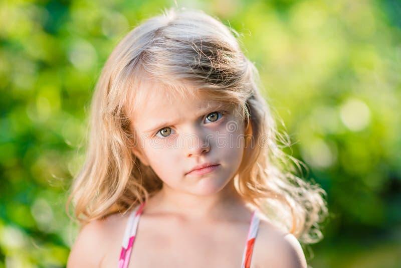 Nahaufnahmeporträt des durchdachten kleinen Mädchens mit dem langen blonden Haar stockfoto