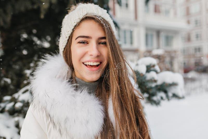Nahaufnahmeporträt des frohen lächelnden Mädchens bei der Strickmützeaufstellung im Freien auf Straße voll des Schnees Nette blon lizenzfreie stockbilder
