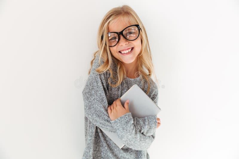 Nahaufnahmeporträt des glücklichen kleinen Mädchens in den Gläsern, die ein Buch umarmen stockfotografie