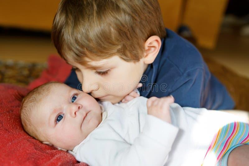 Nahaufnahmeporträt des glücklichen Kleinkindjungen mit neugeborenem Baby, nette Schwester geschwister Bruder und Baby, die streic stockfotografie