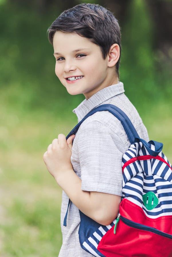 Nahaufnahmeporträt des glücklichen Schülers mit dem Rucksackschauen stockbilder