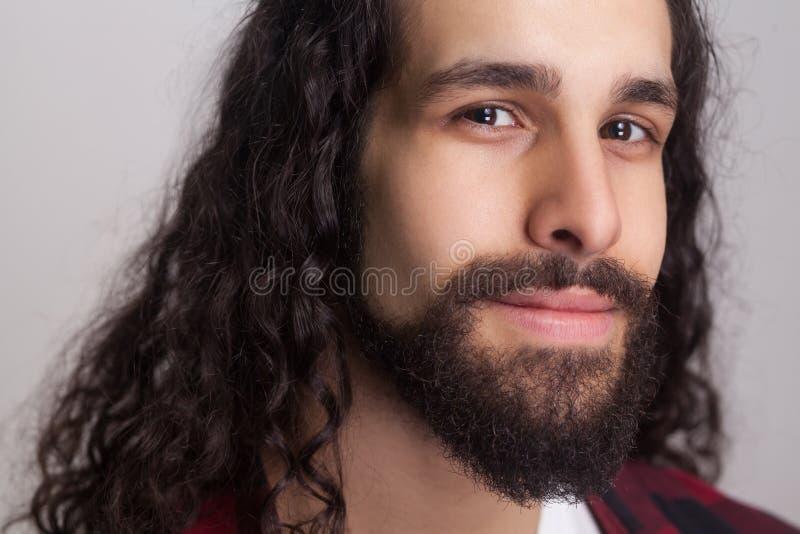 Nahaufnahmeporträt des hübschen überzeugten Mannes mit schwarzem langem gelocktem stockfotos