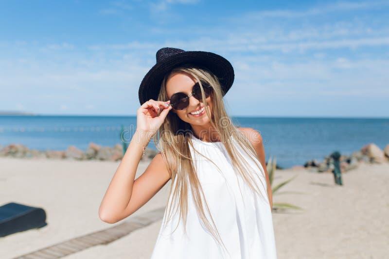 Nahaufnahmeportr?t des h?bschen blonden M?dchens mit dem langen Haar steht auf dem Strand nahe Meer Sie tr?gt den schwarzen Hut,  stockfoto