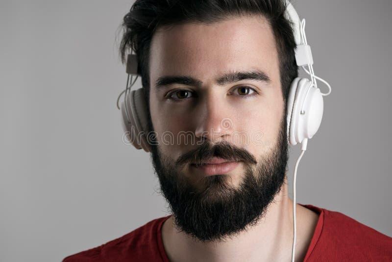 Nahaufnahmeporträt des jungen bärtigen Mannes mit Kopfhörern hörend Musik stockbilder