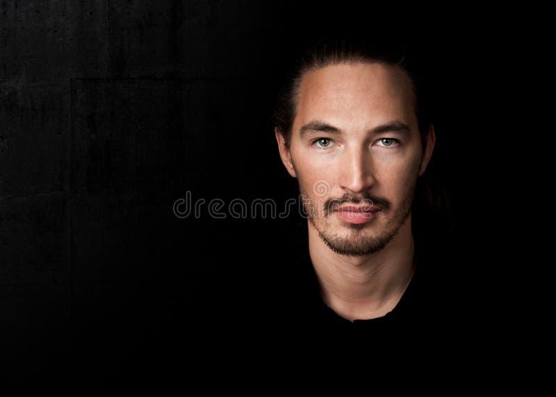 Nahaufnahmeporträt des jungen Mannes über Schwarzem stockbilder