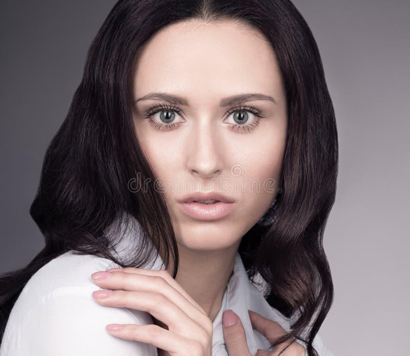 Nahaufnahmeporträt des jungen schönen Mädchens mit einem sinnlichen Blick, der gegen einen grauen Hintergrund aufwirft lizenzfreies stockfoto