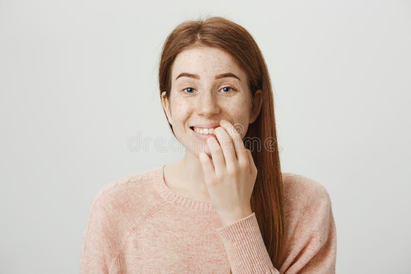 Nahaufnahmeporträt des lustigen emotionalen kaukasischen Ingwermädchens mit schlechter Gewohnheit, beißende Nägel auf Fingern bei lizenzfreies stockfoto