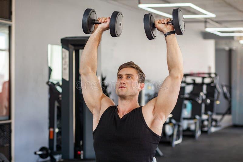Nahaufnahmeporträt des muskulösen errichteten hübschen Athleten des jungen erwachsenen Mannes, der in einer Turnhalle ausarbeitet lizenzfreies stockbild