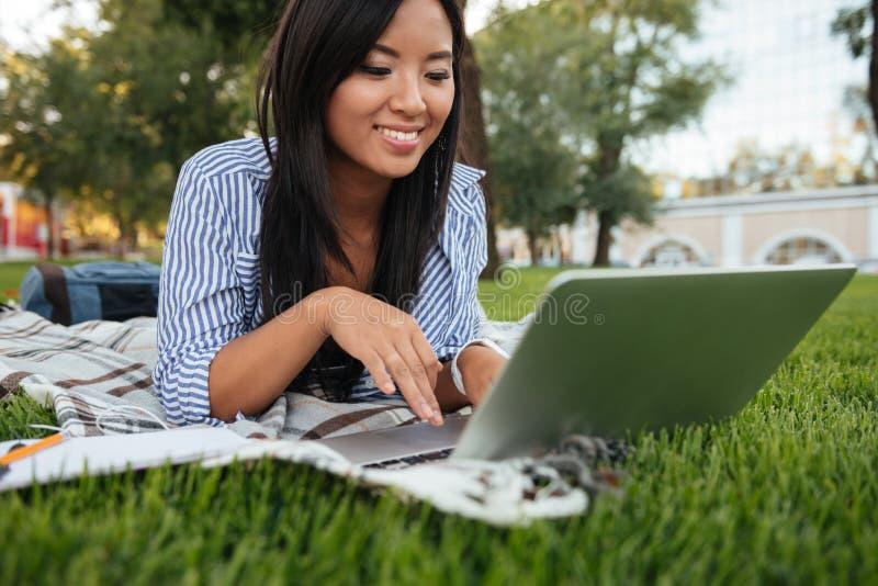 Nahaufnahmeporträt des netten asiatischen Studenten, schreibend auf Laptop, O lizenzfreie stockbilder
