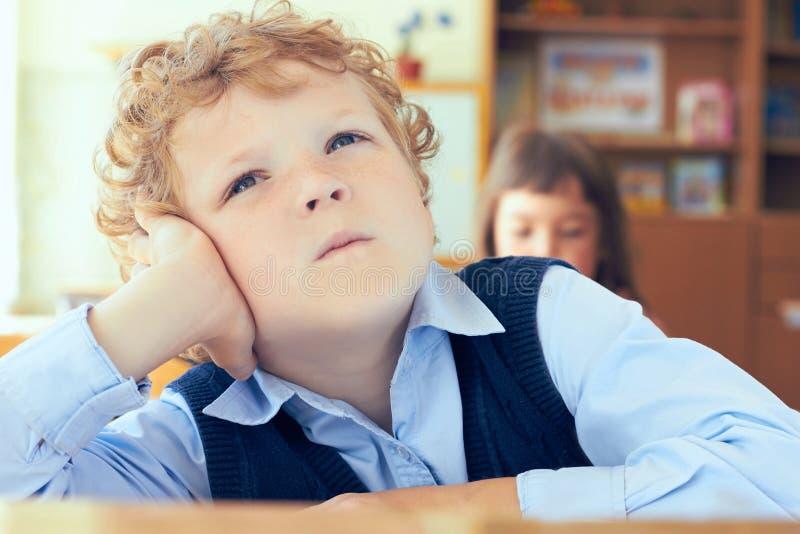 Nahaufnahmeporträt des netten durchdachten Schülers, der am Schreibtisch und am Träumen sitzt stockfoto
