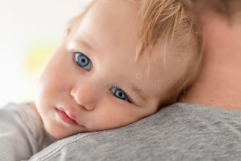 Nahaufnahmeporträt des netten entzückenden blonden kaukasischen Kleinkindjungen auf Vätern schultern zuhause Süße kleines Kinderg lizenzfreies stockfoto