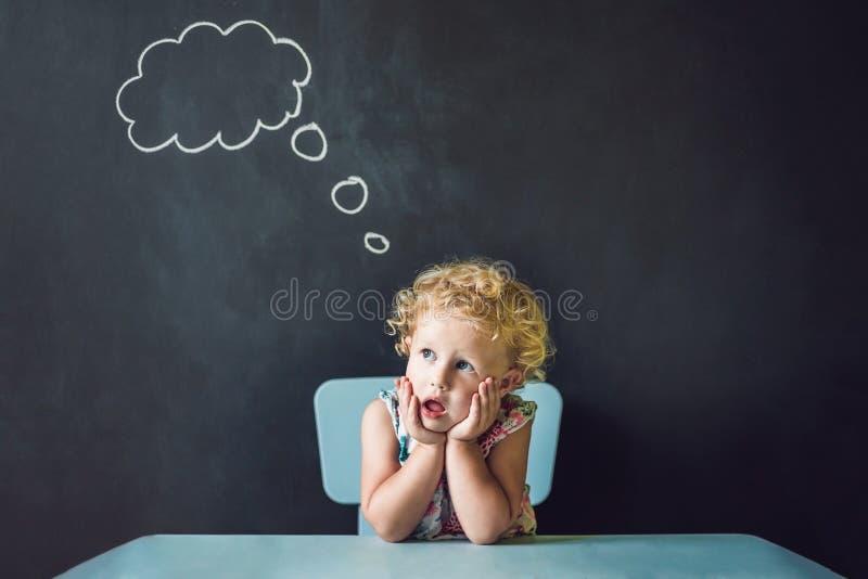 Nahaufnahmeporträt des netten kleinen Mädchens, das tief an somet denkt lizenzfreie stockfotos