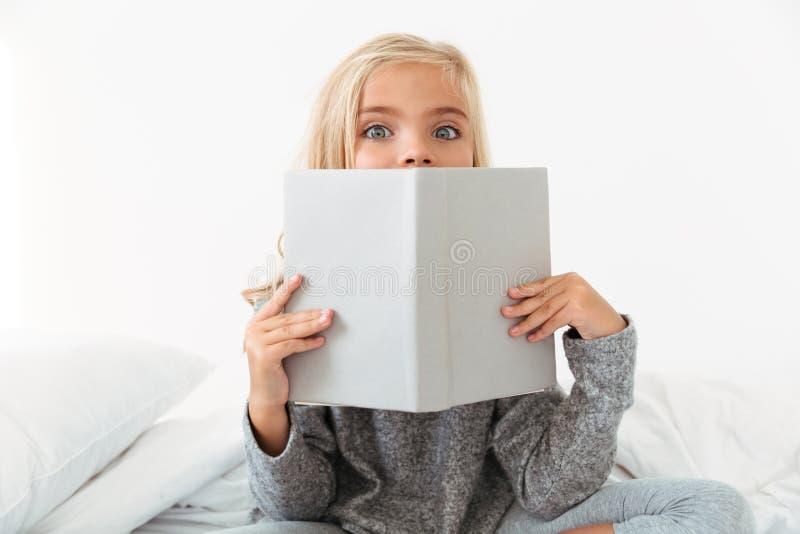 Nahaufnahmeporträt des reizend Mädchens ihr Gesicht mit Buch bedeckend, lizenzfreie stockfotografie