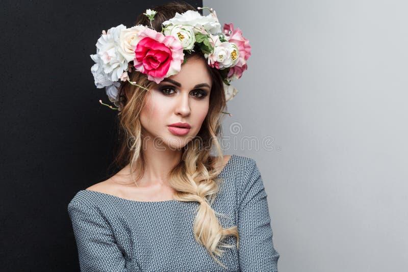 Nahaufnahmeporträt des schönen attraktiven Mode-Modells im grauen Kleid mit Make-up, Frisur und Hauptblumen auf ihrem Kopf, schau stockfoto