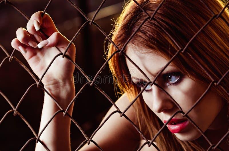 Nahaufnahmeporträt des schönen jungen Mädchens hinter metallischem Gitter stockfotografie