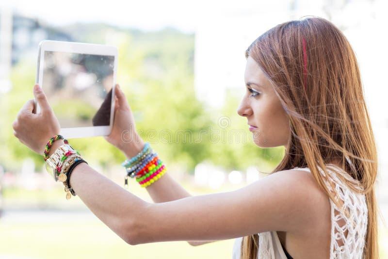 Nahaufnahmeporträt des schönen Mädchens Bilder wiyh Tablette c nehmend lizenzfreie stockbilder
