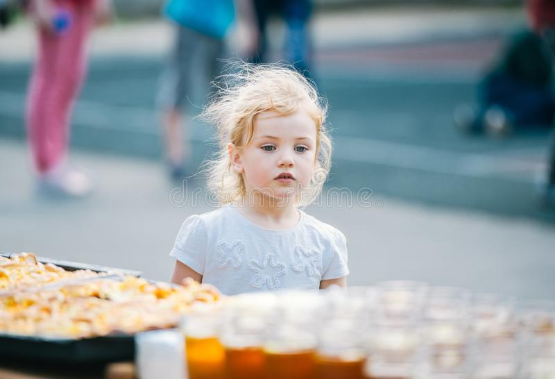 Nahaufnahmeporträt des schönen, netten, kleinen Mädchens, betrachtend Bonbons hungrig lizenzfreie stockbilder
