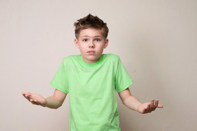 Nahaufnahmeporträt des stummen ahnungslosen verwirrten Jungen, Arme heraus bitten stockfoto