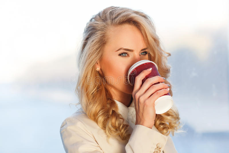 Nahaufnahmeporträt des trinkenden Kaffees der schönen frischen Blondine lizenzfreies stockfoto