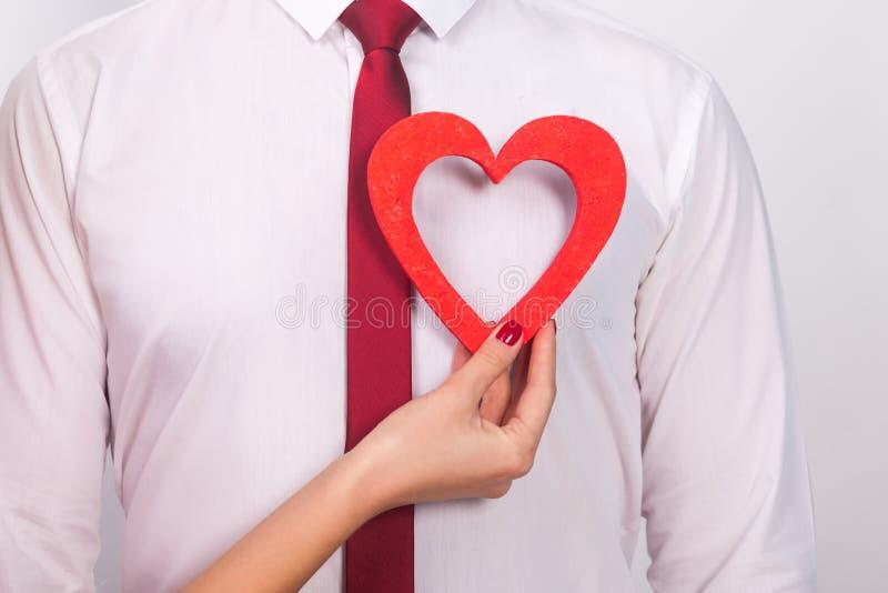 Nahaufnahmeporträt des unbekannten Mannes, Frauenhand, sein Herz halten stockbild
