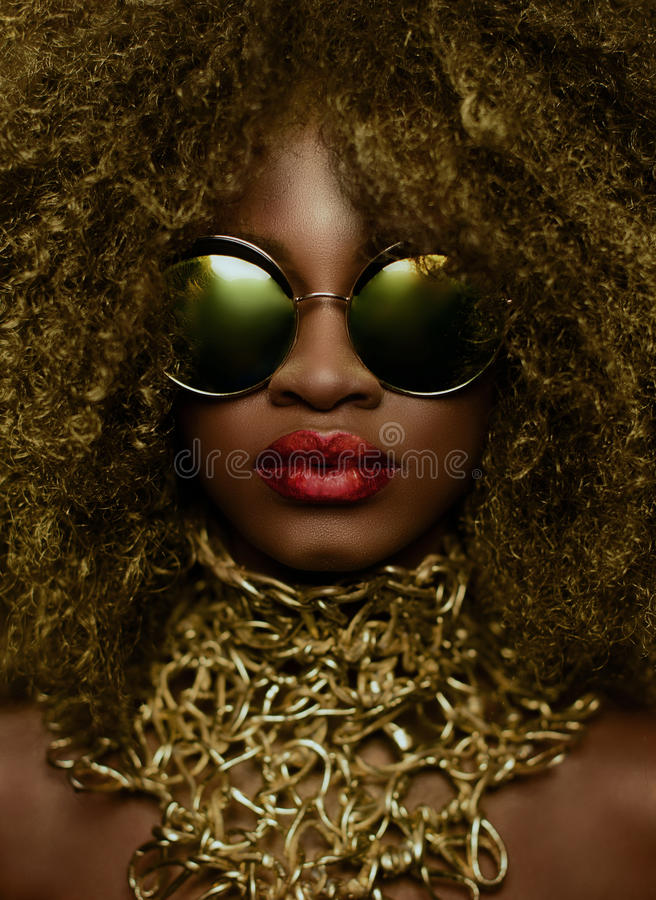 Nahaufnahmeporträt des weiblichen Modells des magischen goldenen Afroamerikaners in der enormen Sonnenbrille mit hellem Funkelnma stockfotos