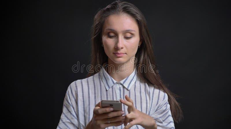 Nahaufnahmeporträt des weiblichen Simsens des jungen schönen brunette Kaukasiers am Telefon vor der Kamera mit lokalisiert lizenzfreie stockfotos