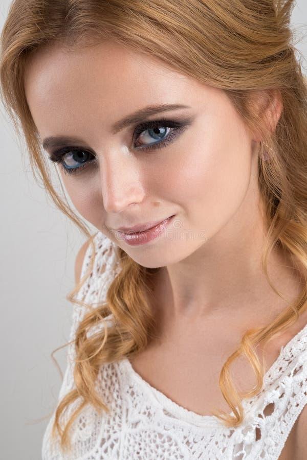 Nahaufnahmeporträt einer Blondine mit blauen Augen und Locken in einem weißen Spitzenoberteil stockfotos