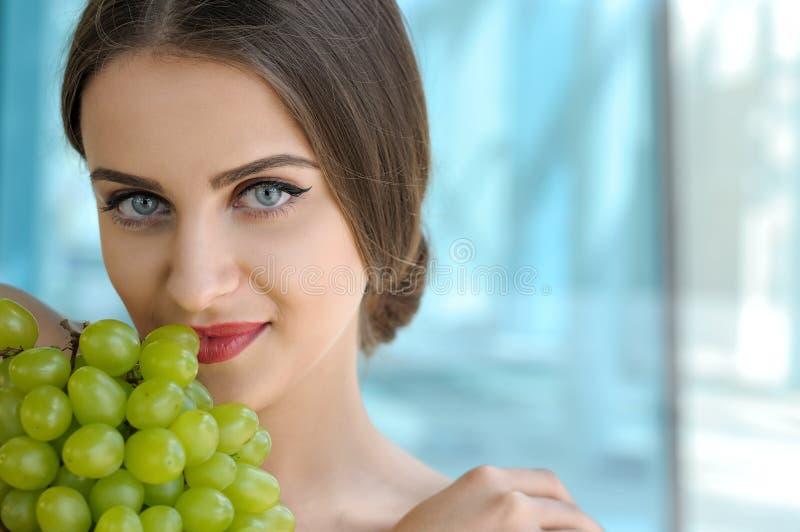 Nahaufnahmeporträt einer Frau, die Trauben hält lizenzfreie stockfotos