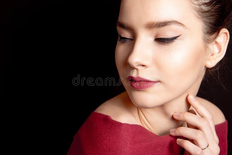 Nahaufnahmeporträt einer Frau mit klassischem Make-up mit einem schwarzen Pfeil und einer bloßen Lippe über ihren Schultern auf e lizenzfreies stockfoto