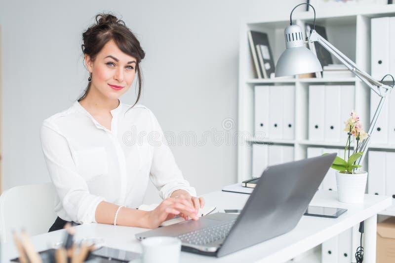 Nahaufnahmeporträt einer Geschäftsfrau an ihrem Arbeitsplatz, der mit PC, in camera schauend, tragender Büroanzug arbeitet stockbild
