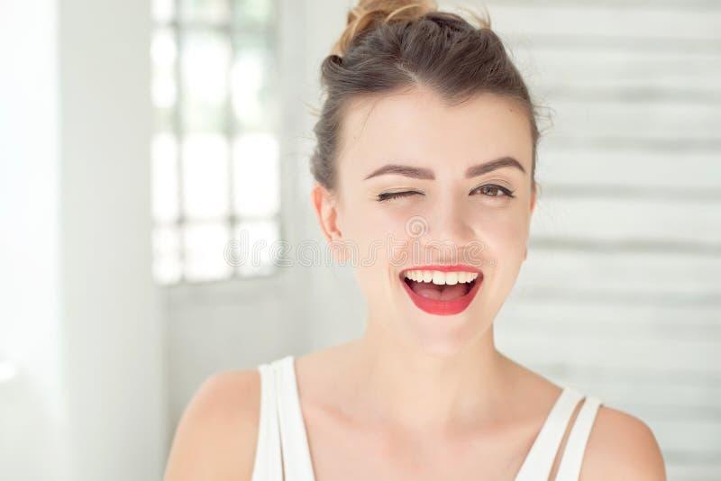 Nahaufnahmeporträt einer glücklichen jungen lächelnden und blinzelnden Frau Perfekte Haut mit Sommersprossen, gewelltes gesundes  stockbilder